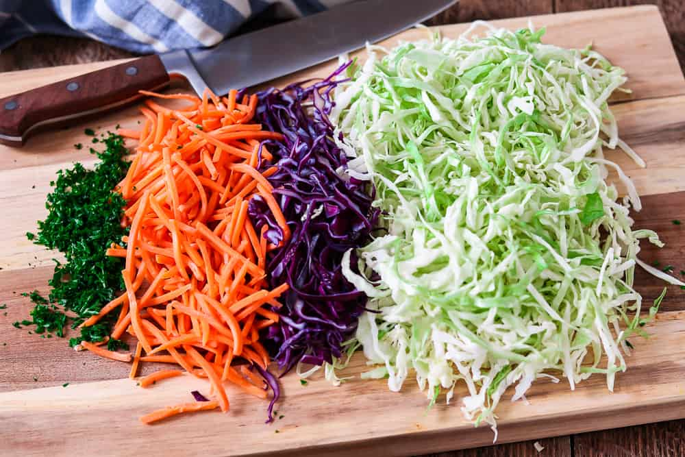 Shredded cabbage, carrots and chopped parsley on a wooden cutting board.
