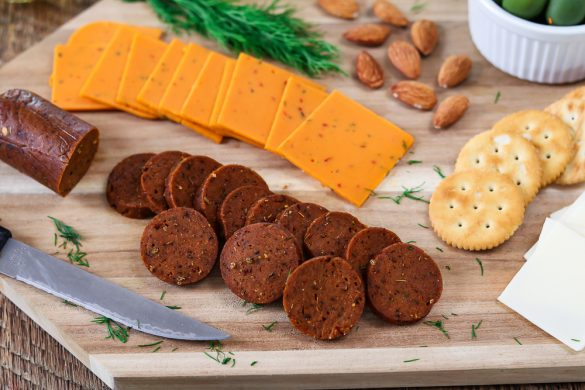 Wood cutting board with cheese, crackers, almonds and vegan pepperoni White wine on the side.