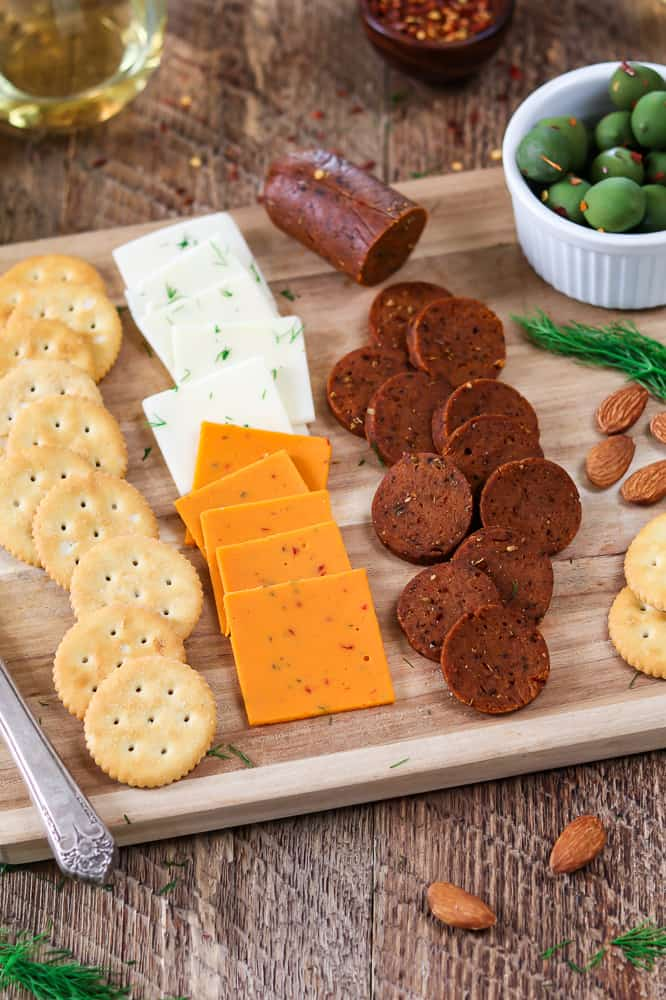 Vertical view of vegan cheese, olives, crackers and vegan pepperoni recipe on a wooden cutting board.