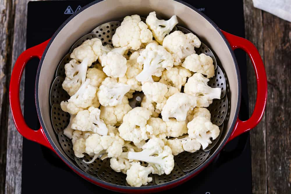 Steaming the cauliflower florets in a red pot.