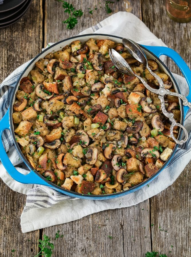 Vegan Sourdough Bread Stuffing in a blue casserole dish. Topped with fresh-cut parsley.