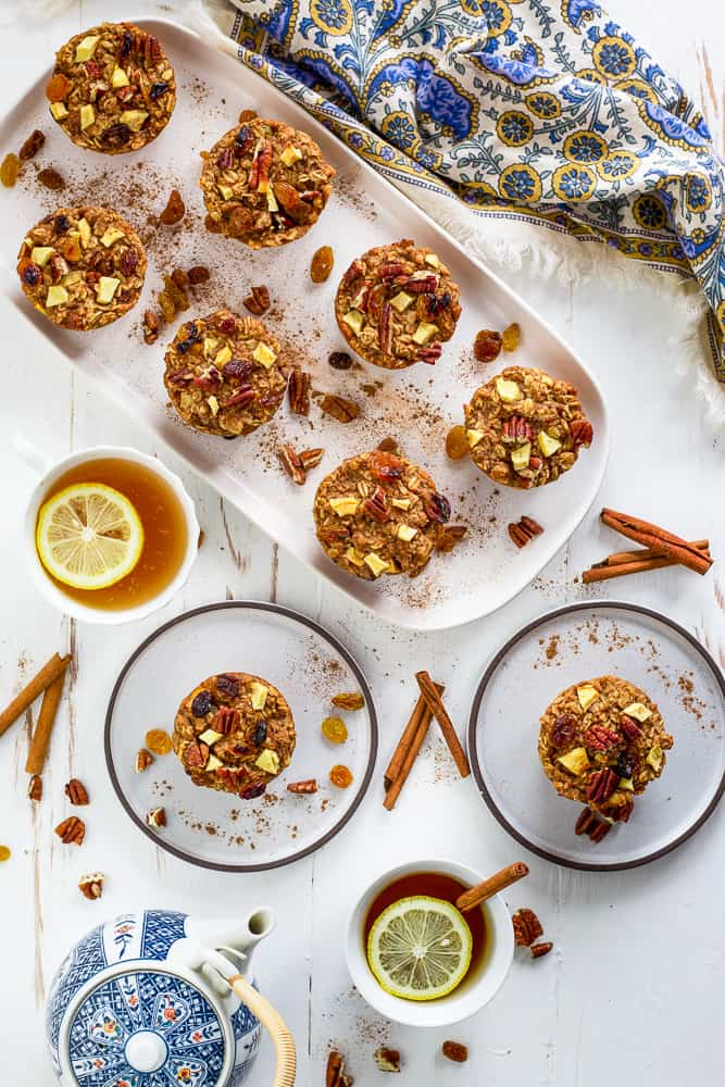 Overhead view of baked oatmeal muffins on a white serving tray. Tea with lemon on the side.