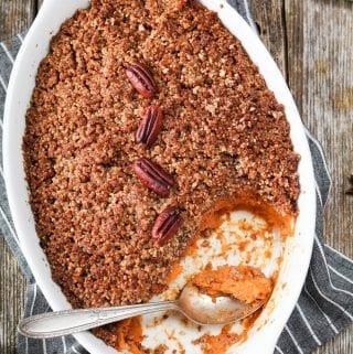 Overhead view of sweet potato casserole in a white serving dish. Small plates on the side.