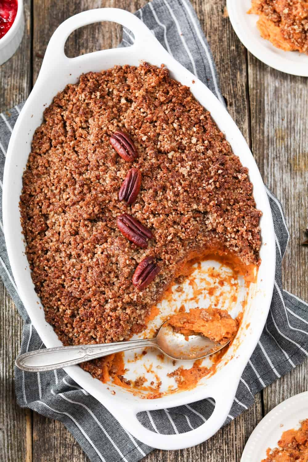 Fully baked sweet potato casserole in a white baking dish with spoon inside.