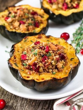 stuffed acorn squash on a white serving platter. Topped with fresh thyme.