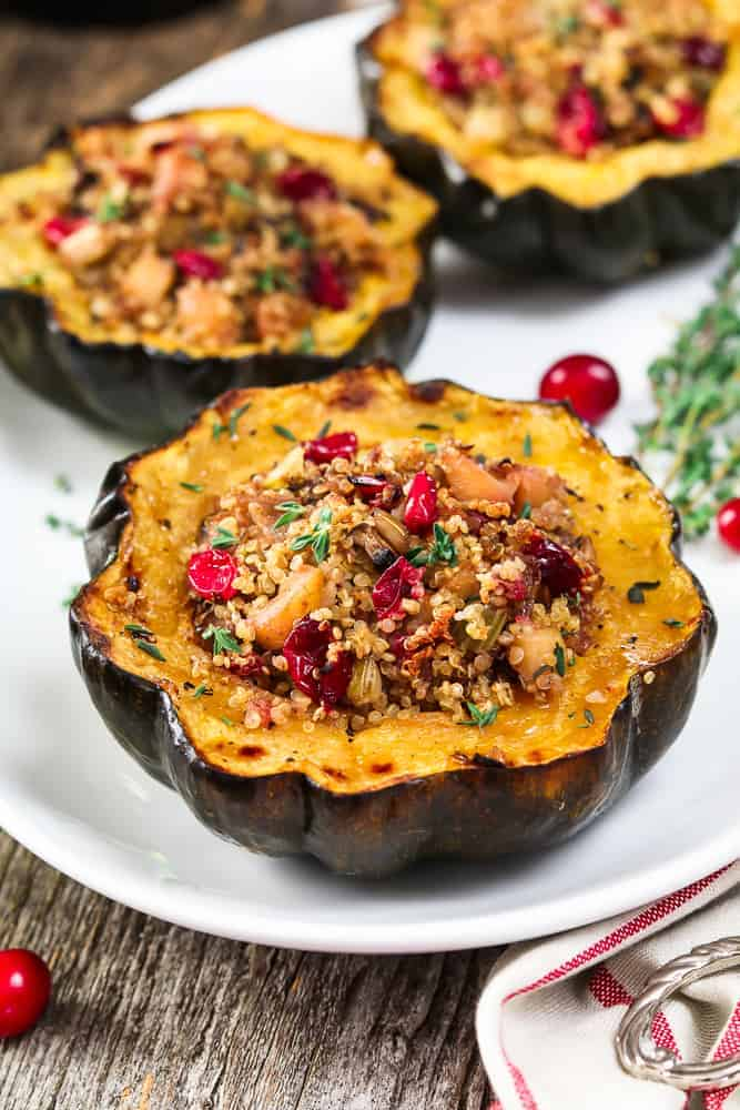 Three pieces of stuffed acorn squash on a white serving platter. Fresh cranberries and thyme on the side.