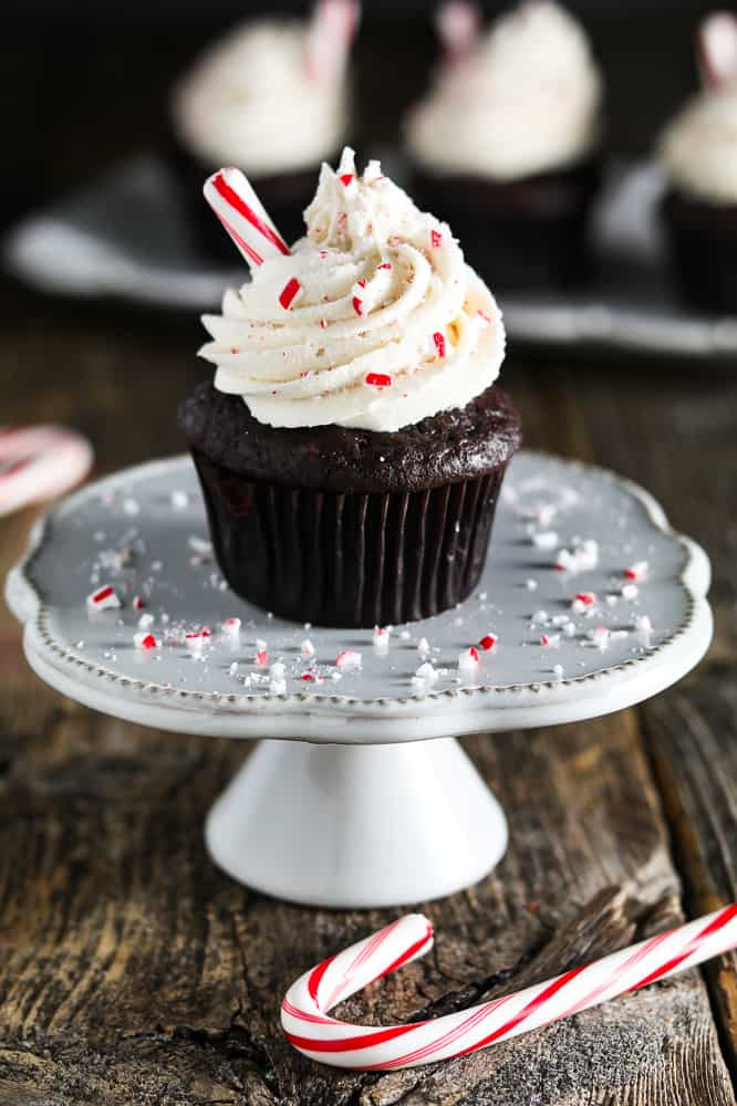 decorated chocolate cupcake on white cupcake stand. Crushed candy cane on the stand.