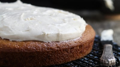 side view of vegan cream cheese frosting partially on a baked cake.