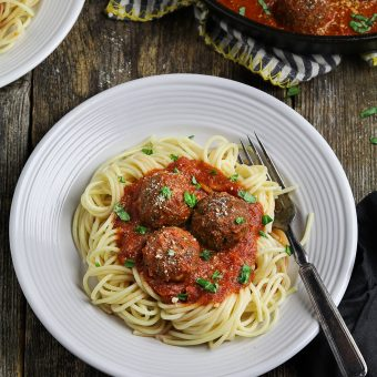 vegan meatballs on top of spaghetti with a fork on the side.