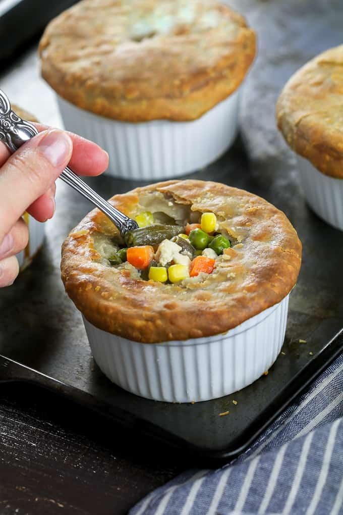 Close up view of a spoon breaking into a vegan pot pie.
