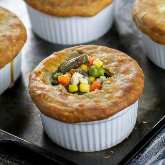 four fully baked vegan pot pies in a ramekin. Closeup shot of one vegan pot pie with veggies popping out the top.