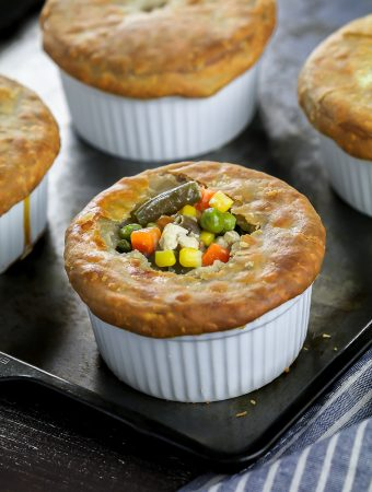 four fully baked vegan pot pies in a ramekin. Closeup shot of one vegan pot pie with veggies popping out the top.