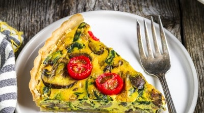 One slice of vegan quiche on a white plate. Tomatoes in a bowl on the side with full quiche.