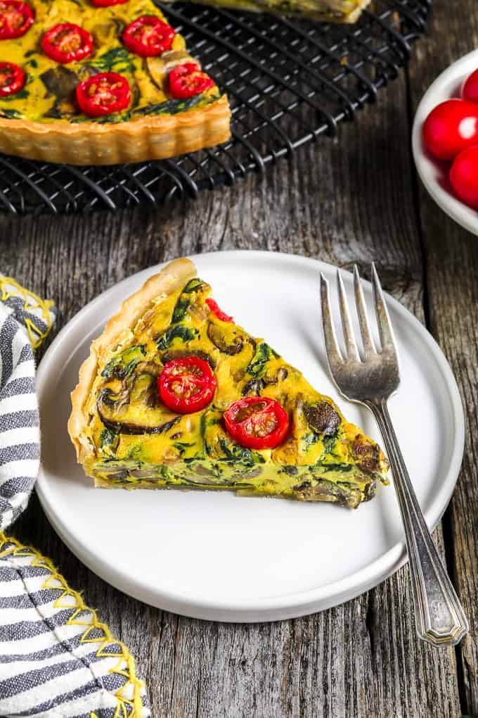 one slice of vegan quiche on a white plate with fork on the side. Full quiche in the background on a cooling rack.