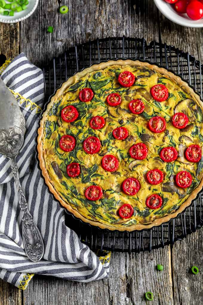 Overhead view of easy vegan quiche on a cooling rack with pie server and striped napkin on the side.