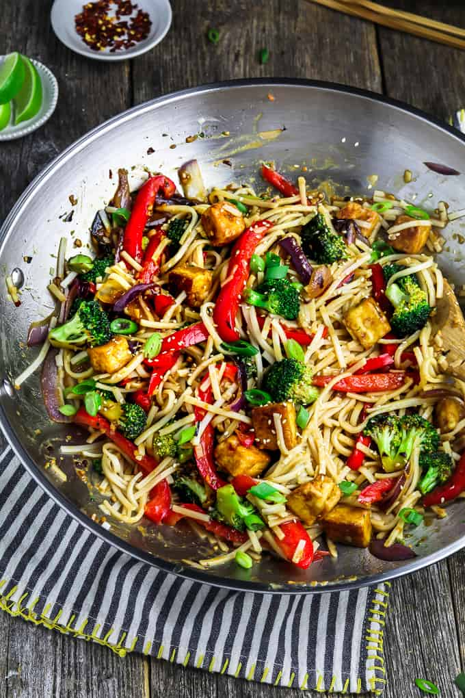 wok filled with fully cooked tofu veggie stir fry and topped with green onion. Lime wedges on the side.