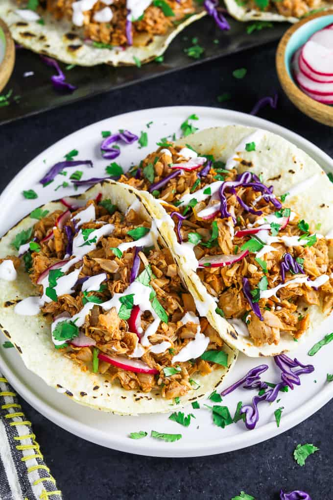 Two fully assembled tacos on a white plate. Topped with red cabbage, cilantro and vegan sour cream.