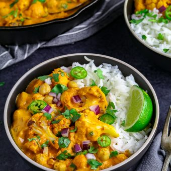Two bowls of chickpea curry, topped with red onion and lime.