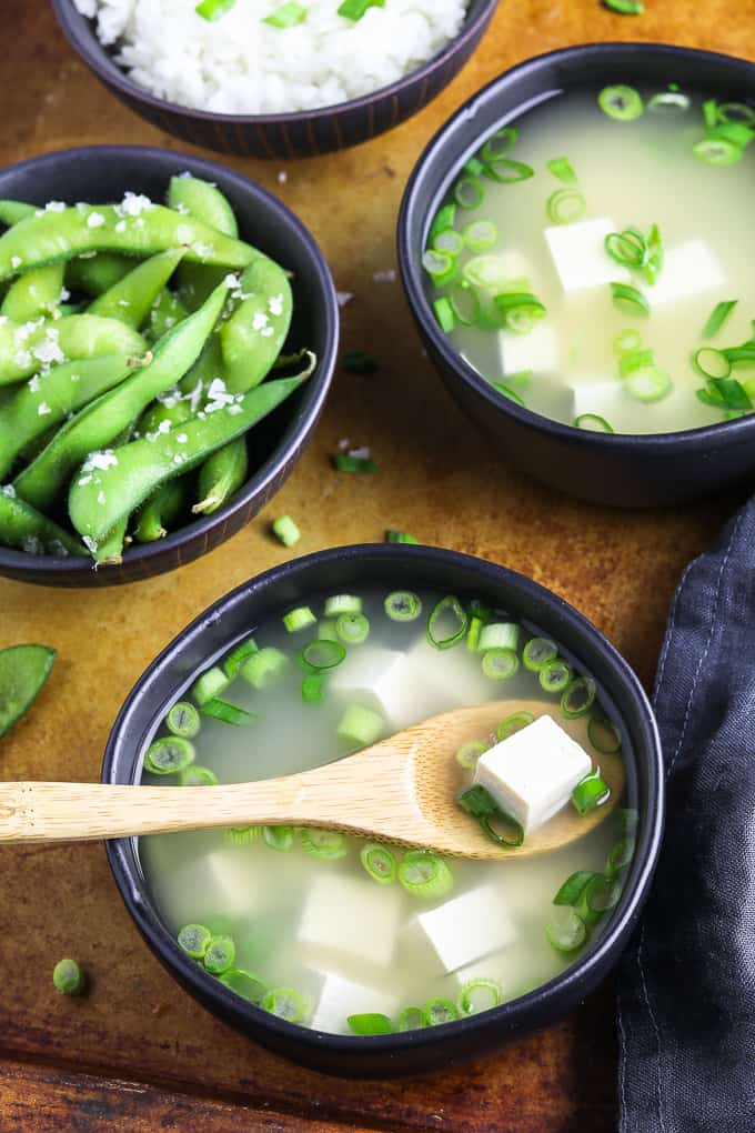 two bowls of miso soup on a serving tray with rice and edamame on the side.