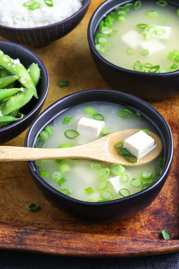 two bowls of miso soup on a serving tray with two bowls of rice and edamame on the side.