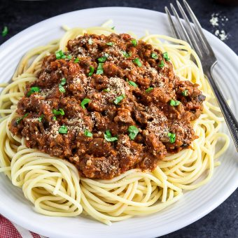 white plate topped with pasta and vegan bolognese sauce.