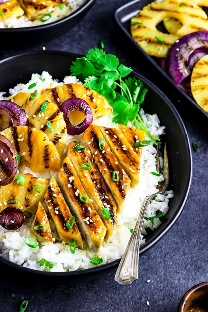 Side view of a black bowl with grilled tofu, pineapple and onion on top of white rice.