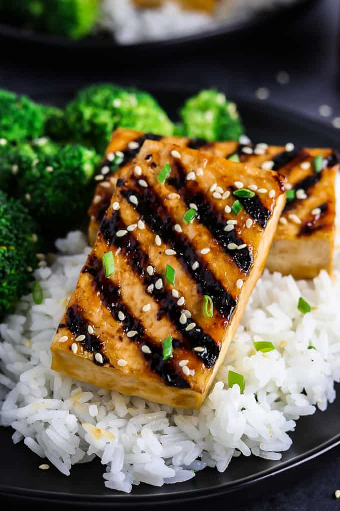 close up view of a piece of tofu on a bed of rice.