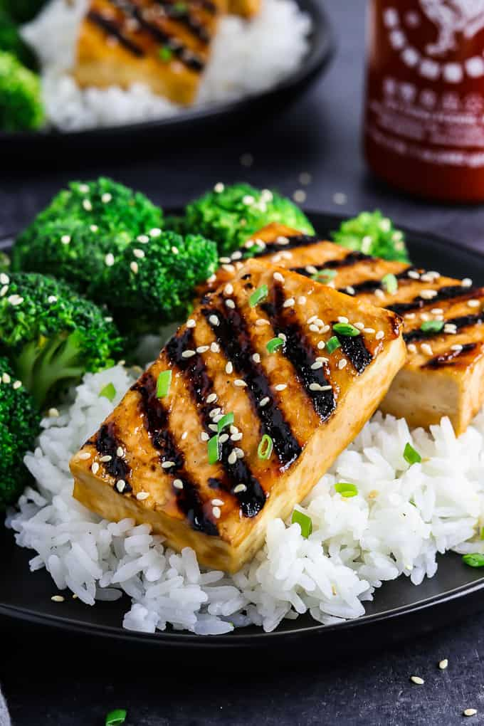 side view of grilled tofu on a black plate on top of rice. Hot sauce in the background.