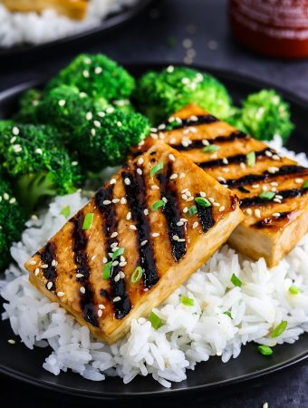 two pieces of grilled tofu on a bed of rice and a side of broccoli.