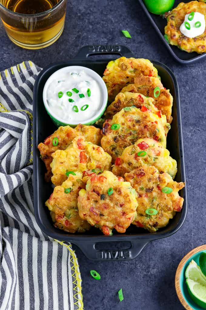 Overhead view of corn fritters in a black serving dish with dip on the side.