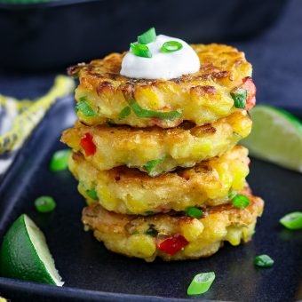 stack of four vegan corn fritters on a black plate with lime wedges on the side.