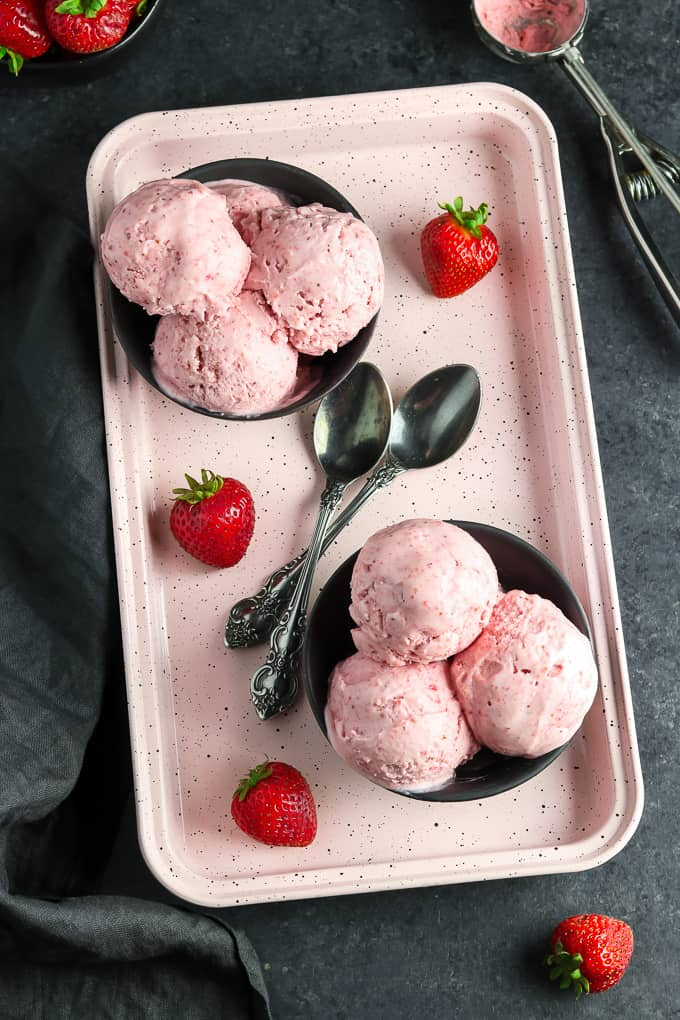 Overhead view of two bowls of vegan strawberry ice cream on a tray.