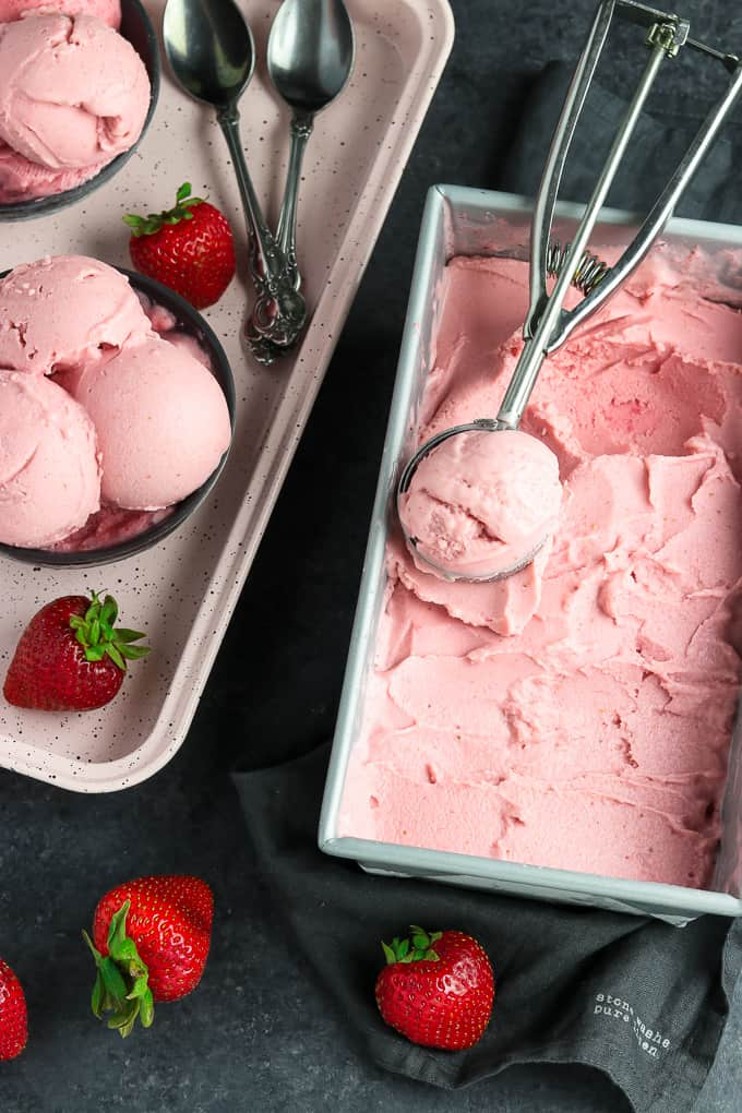 Container filled with strawberry ice cream with scoop on top.