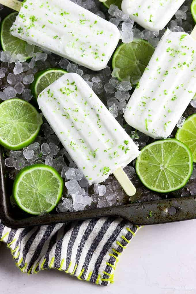 4 coconut lime popsicles on a baking tray with ice and lime slices.