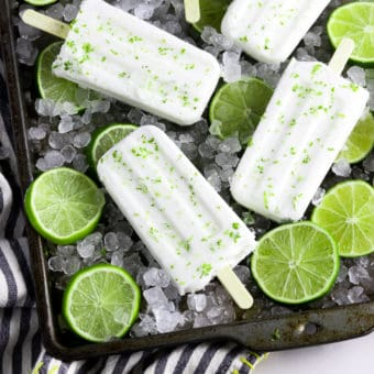 Overhead view of coconut lime popsicles on a baking tray with ice.