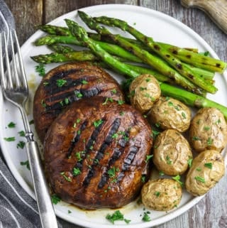 overhead view of two portobello mushroom steaks on a white plate. Asparagus and potatoes on the side.