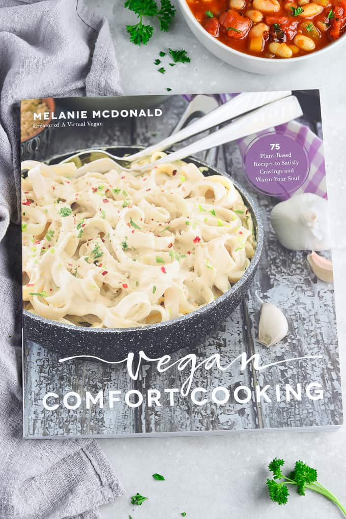 Photo of Vegan Comfort Cooking Cookbook with tomato soup in the background.