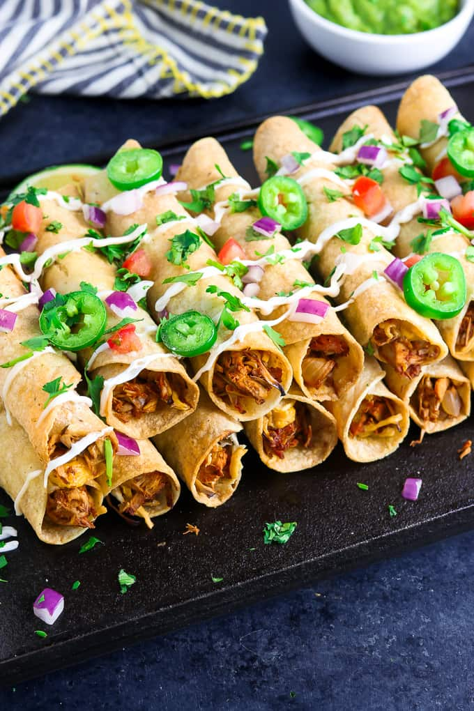 Side view of stacked baked taquitos on a black tray with guacamole in the background.
