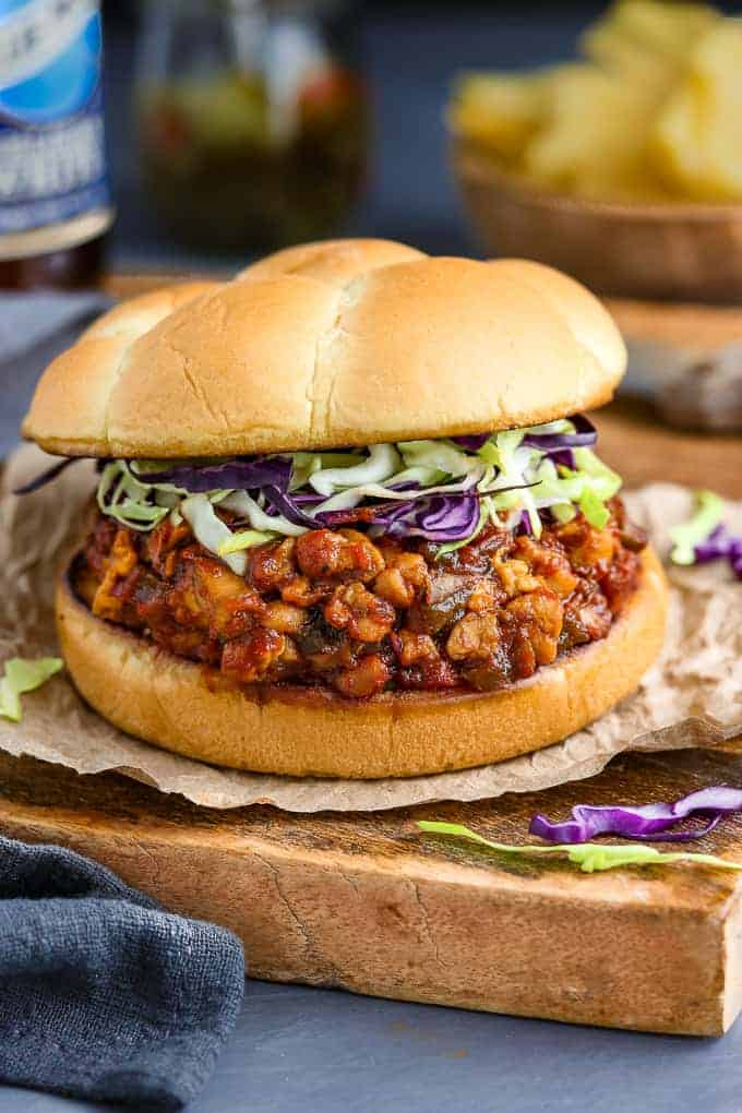Vegan Sloppy Joes on a wood cutting board with chips, relish and bottle in the background.