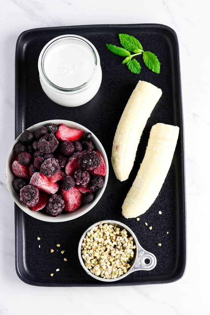 Ingredients for smoothie bowl on a black serving tray.