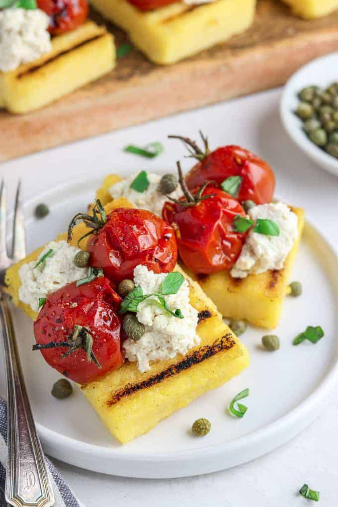 Side view of grilled polenta on a white plate with capers in the background.