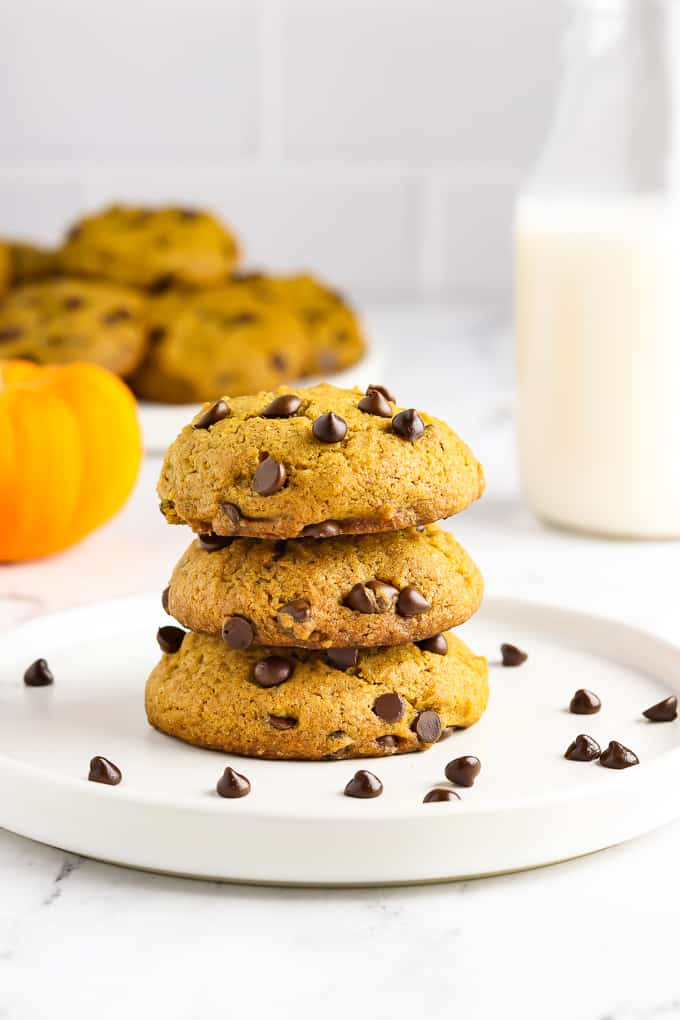 3 pumpkin chocolate chip cookies stacked on a white plate with milk in the background.