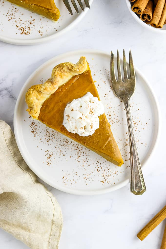One slice of vegan pumpkin pie on a white plate with a fork on the side.