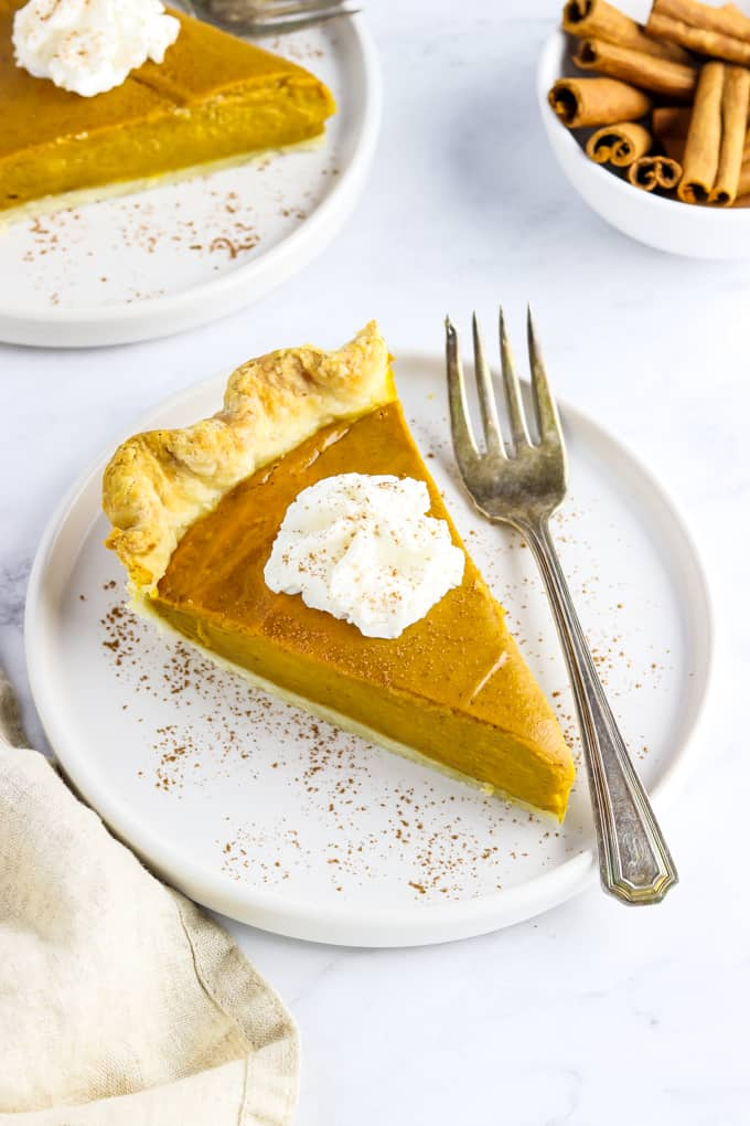 Slice of pie on a white plate with whipped cream on top and fork on the side.