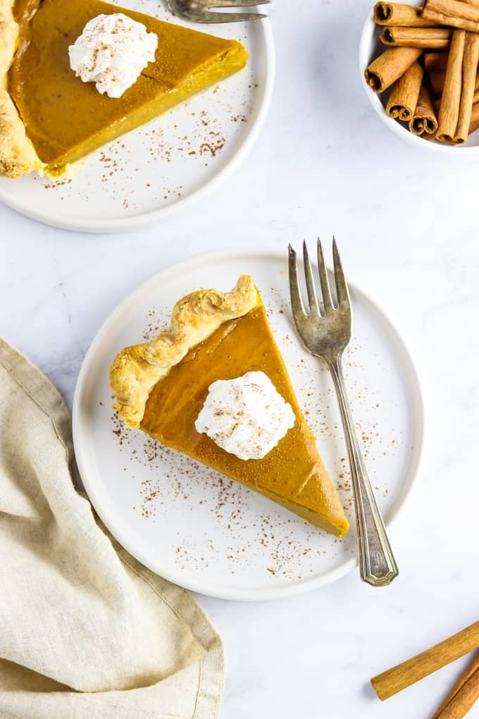 Overhead view of two slice of vegan pumpkin pie on white plates with forks on the side.