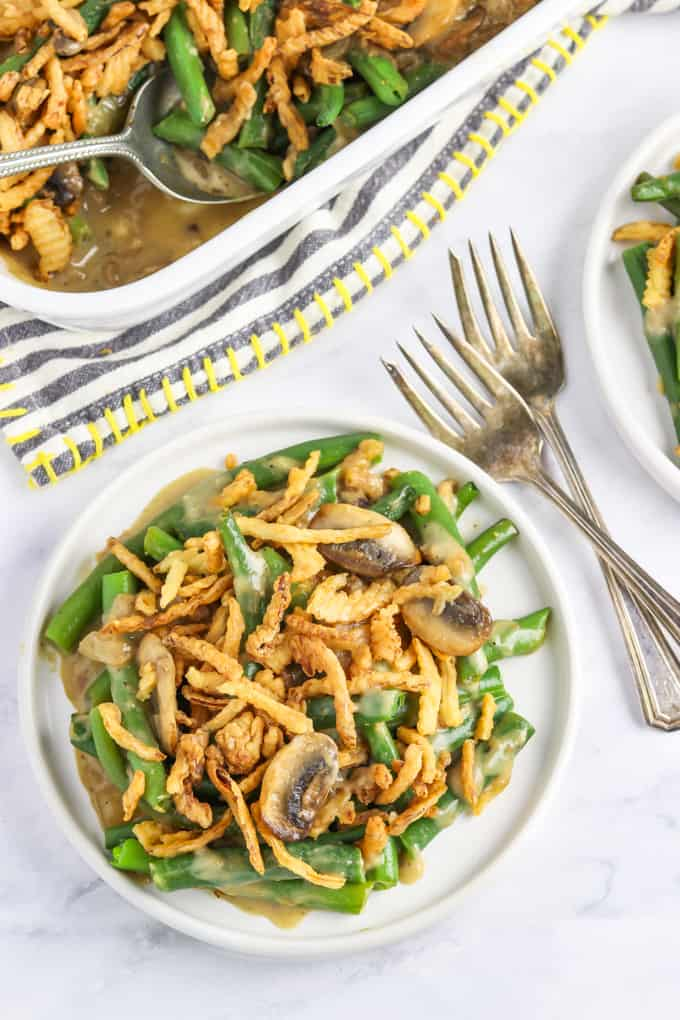 Close up view of vegan green bean casserole on a white plate. Forks on the side.