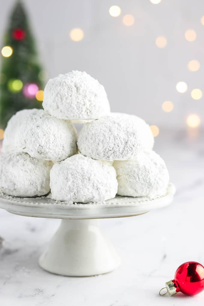 close up view of a stack of vegan snowball cookies on a cake stand.