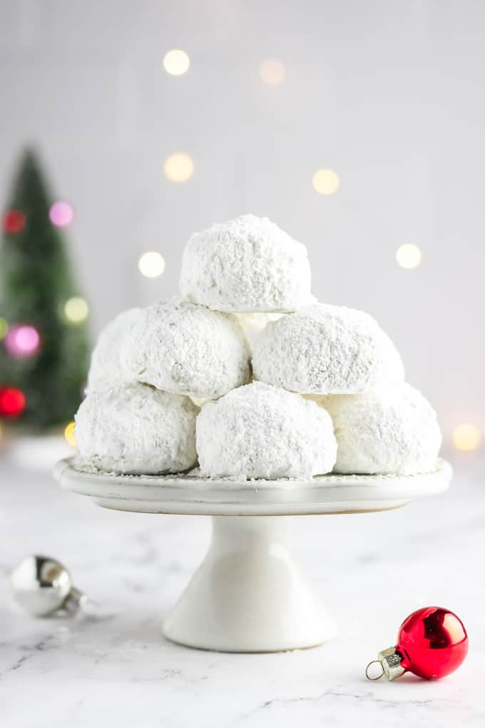 A stack of vegan snowball cookies on a stand with lights in the background.