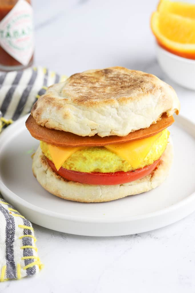 Fully assembled vegan breakfast sandwich on a white plate. Tabasco sauce and orange in the background.