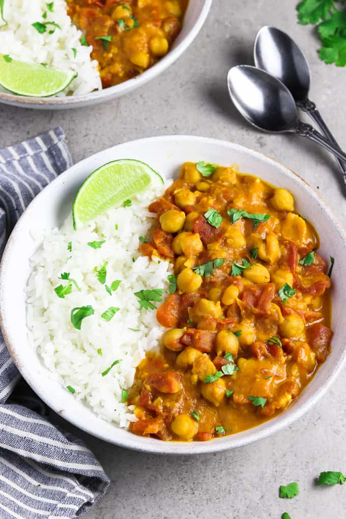Vegan chickpea curry in a white bowl with a striped napkin on the side.